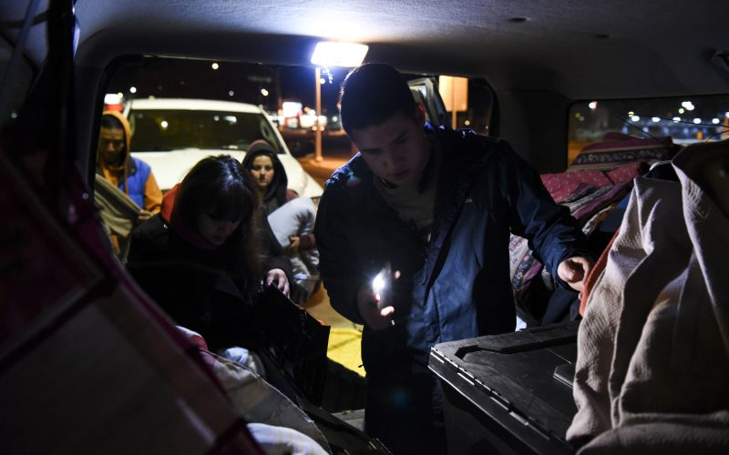 Two volunteers with the Hellfighters Ministry look through bins of donated clothing in the back of a van on February 2, 2019. Two homeless people wait patiently behind them, hoping they will find a jacket, pants, or underwear in their size. /Photo by Celia Raney/ NM News Port