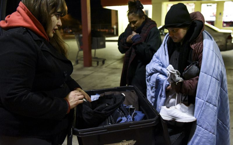 A homeless woman looks through a box of jeans with Jacqui Boyd on Feb. 2, 2019, when the Hellfighters Ministry makes their second stop of the night. /Photo by Celia Raney/ NM News Port