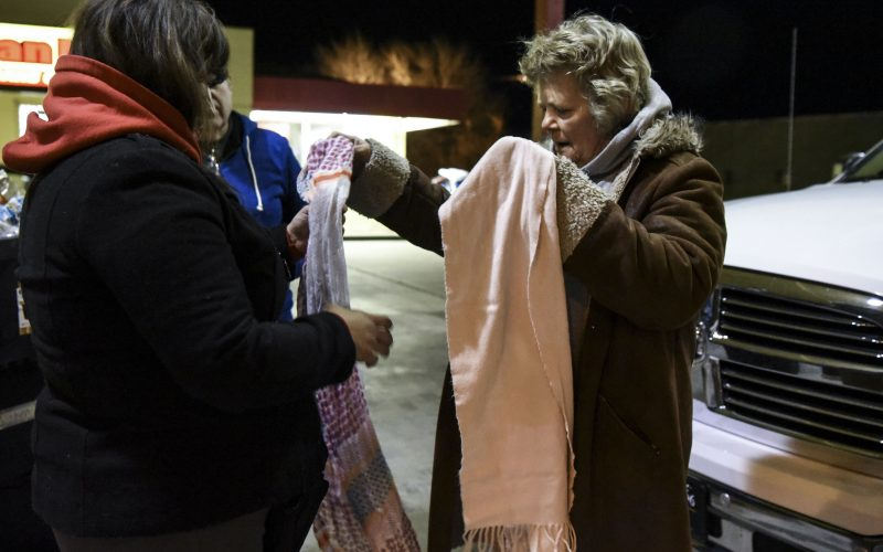 Jacqui Boyd helps a homeless woman pick out a scarf from the back of a van full of donated clothing on Feb. 2, 2019. /Photo By Celia Raney/ NM News Port