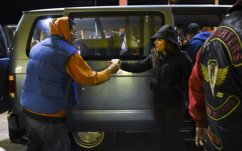 At a gas station on Central Avenue near Louisiana Boulevard, a volunteer with the Hellfighters Ministry hands out hot chocolate and soup to homeless people on February 2, 2019. /Photo by Celia Raney/ NM News Port