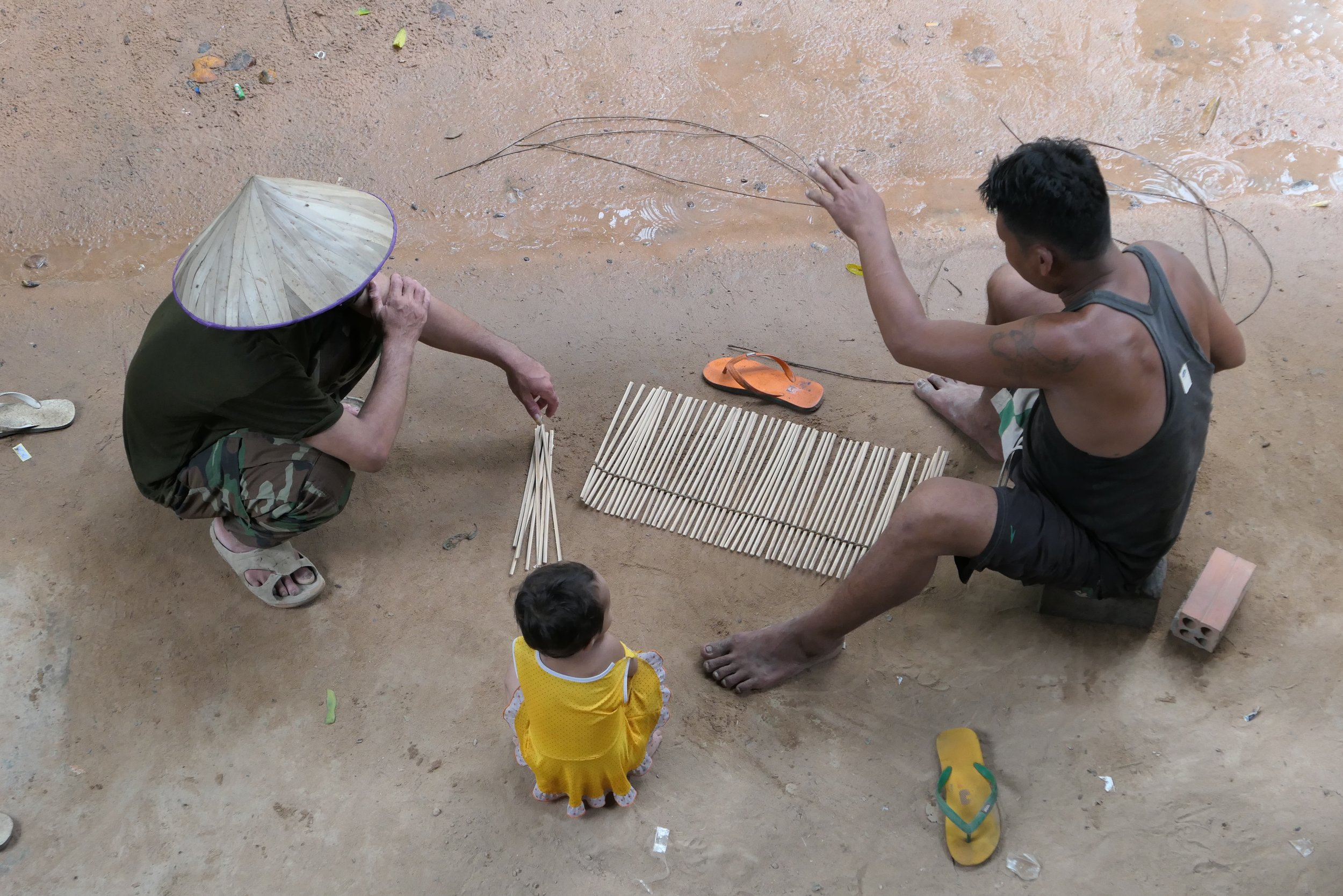 Sarou's brother-in-law and a local friend demonstrating a traditional bamboo weaving technique used to build various crafts such as window shades or frog traps.