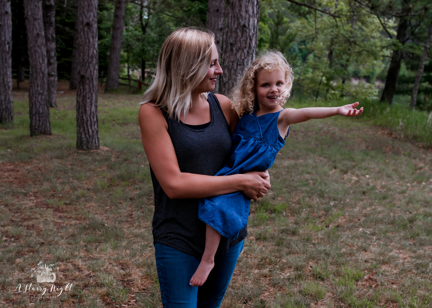 Little girl walking with her mother during their family portrait session that the park.