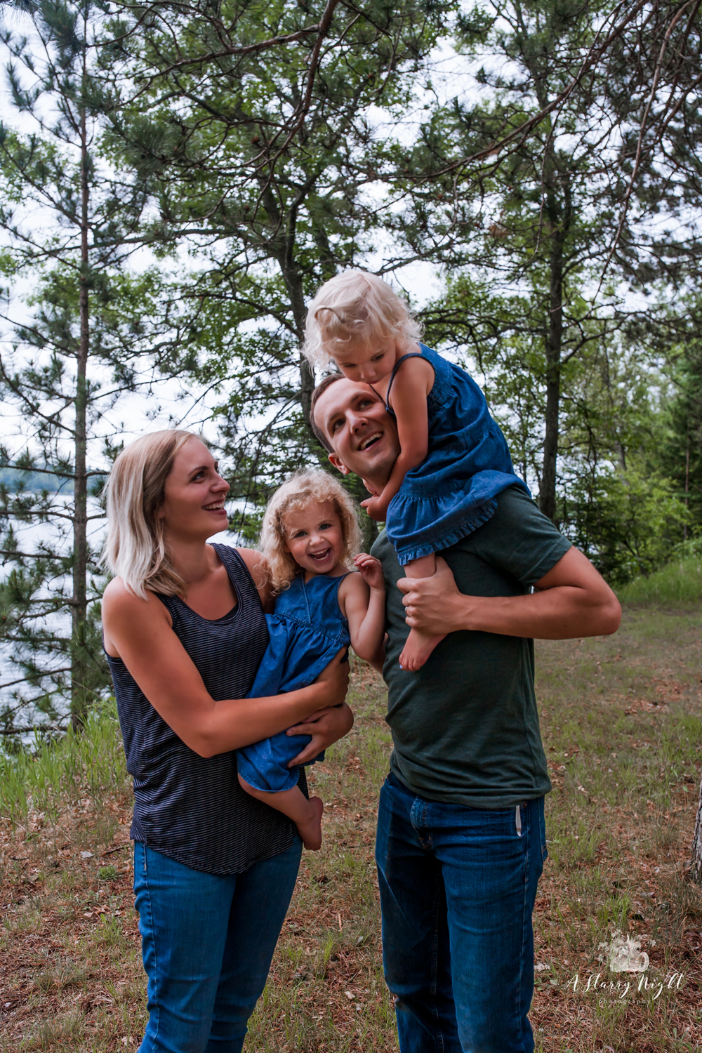 Mom and Dad with their two girls in the pines at Alcona State Park Campground.