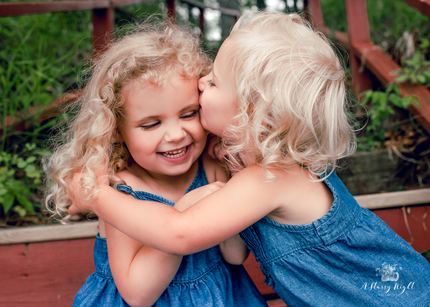 Sister hugging during their family portraits and photography session at Alcona State Park on the lake in Glennie, MI.