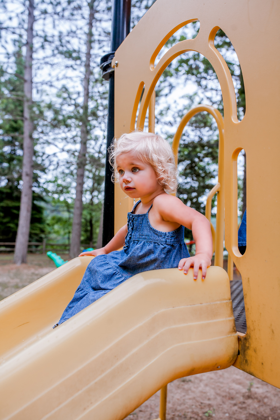 Toddler riding down the slide at playground Alcona State Park in Glennie, MI.