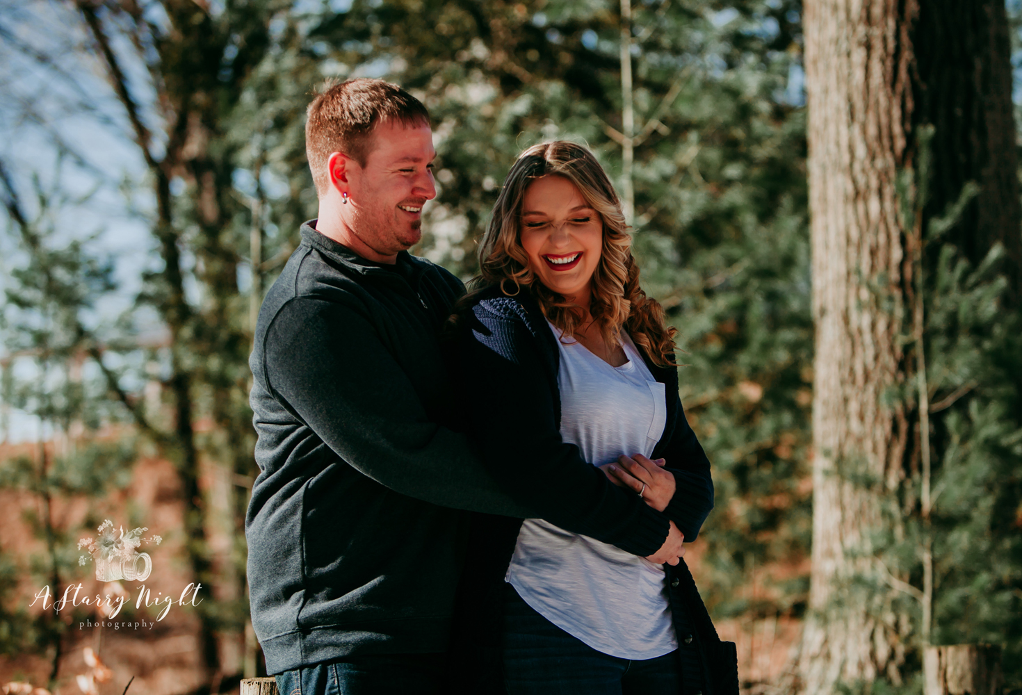 Couple laughing during their enagagement session in Gladwin, MI at the Crooked River Weddings Barn Venue.