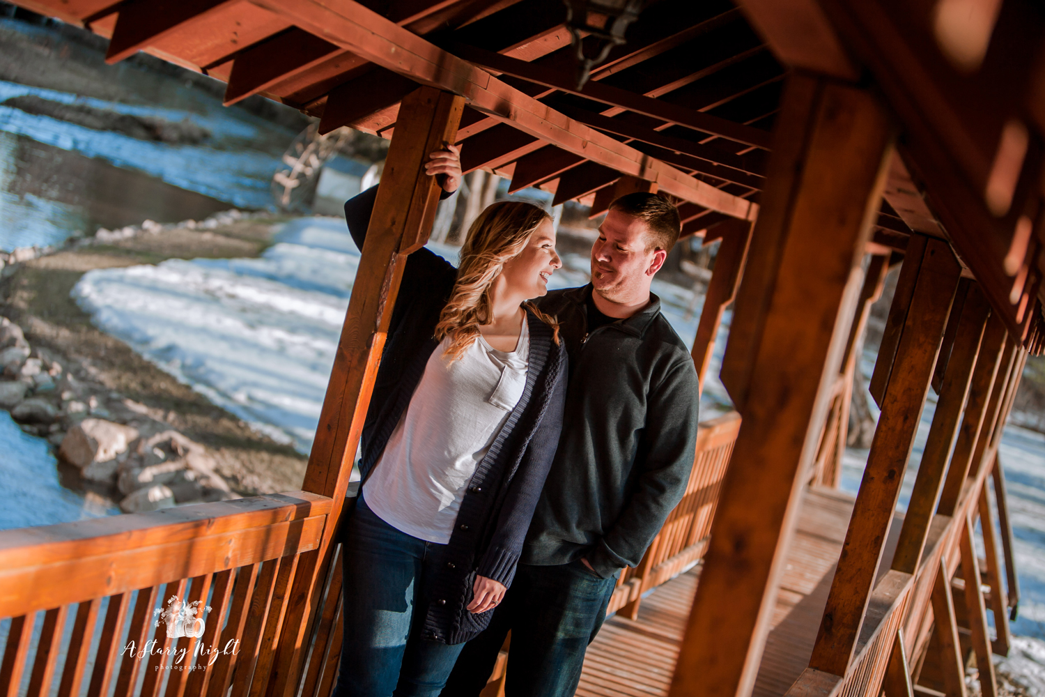 Engaged couple on the Bridge at the Crooked River Barn venue in Beaverton, MI