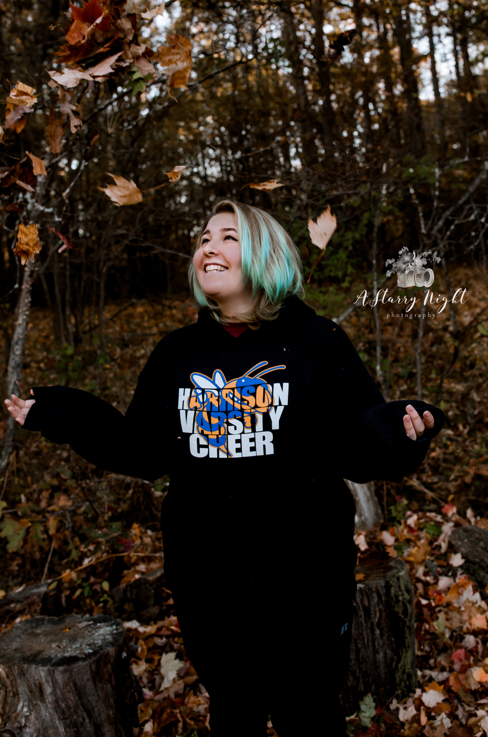 Senior girl from Harrison High School throwing leaves up in the air during her portrait session in Harrison, MI.