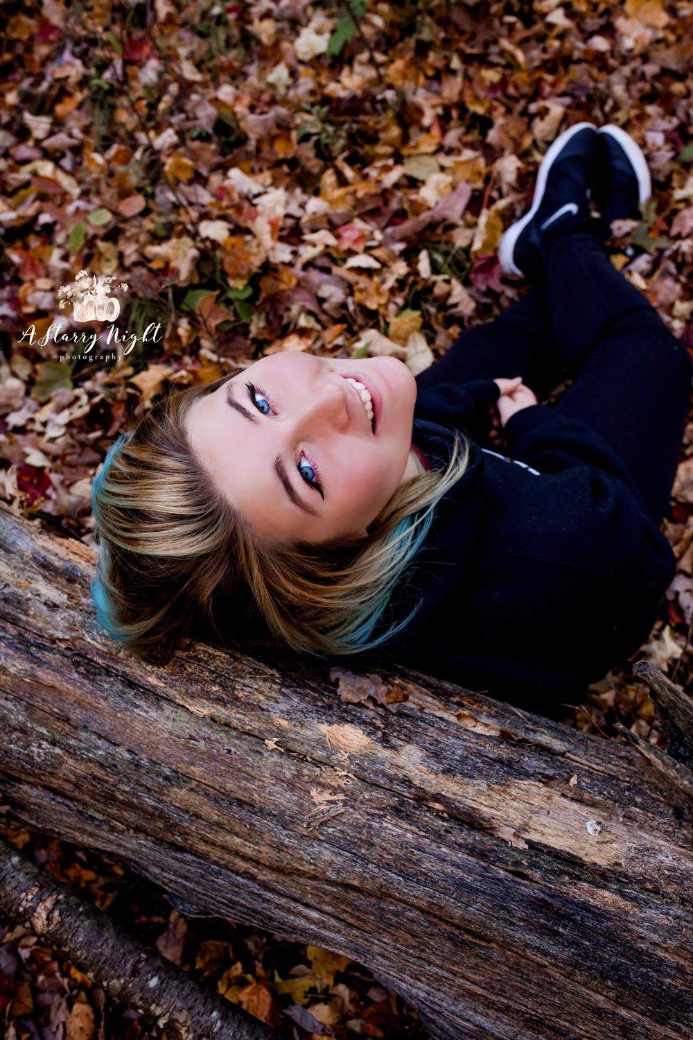 Blue eyed senior girl from Harrison MI High School and her fine art lifestyle portrait against a fall tree.