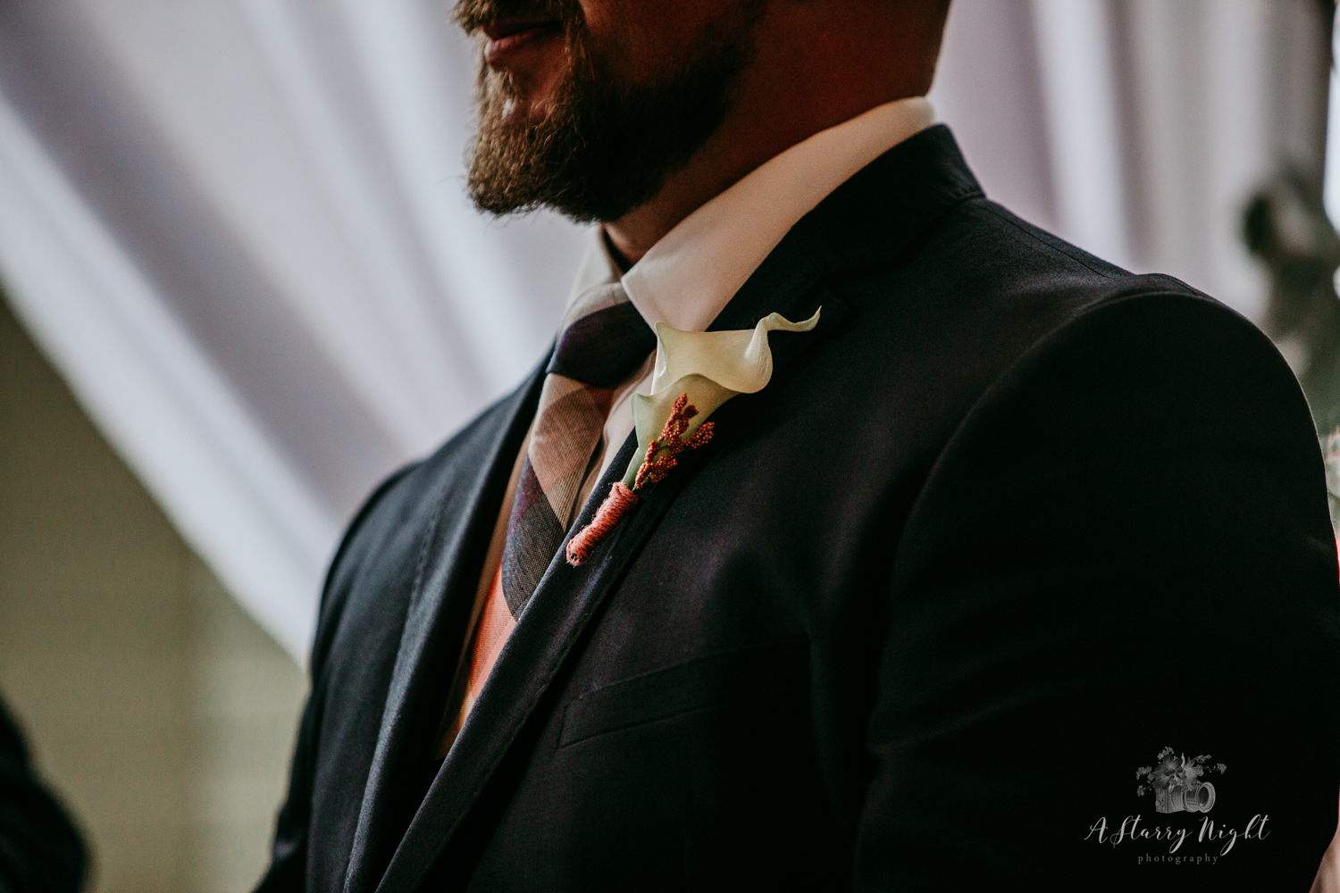 Groom's tuxedo, tie, and boutonniere during wedding ceremony