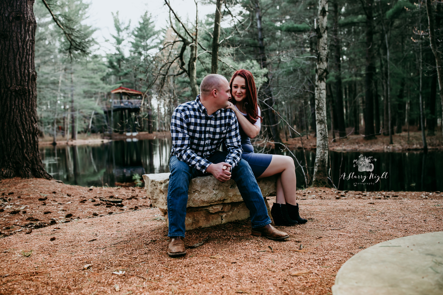Engaged couple sitting on a rock bench at Whiting Forest in Midland, MI.