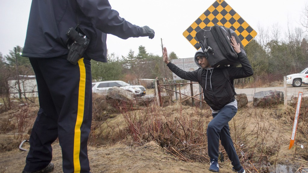An RCMP officer warns a man to cross at the legal border crossing or he will be arrested at the border from New York into Canada on Wednesday, March 8, 2017 in Hemmingford, Quebec. (THE CANADIAN PRESS/Ryan Remiorz)
