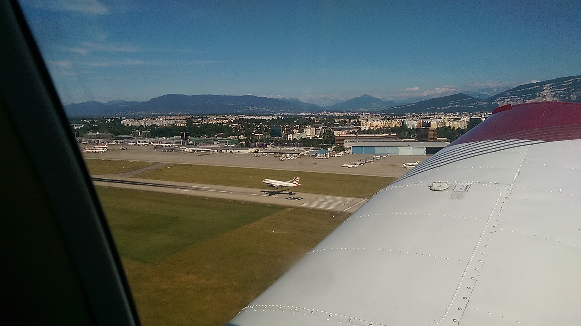 A British Airways about to land on Geneva's main runway, as we are on Final Approach to the grass.