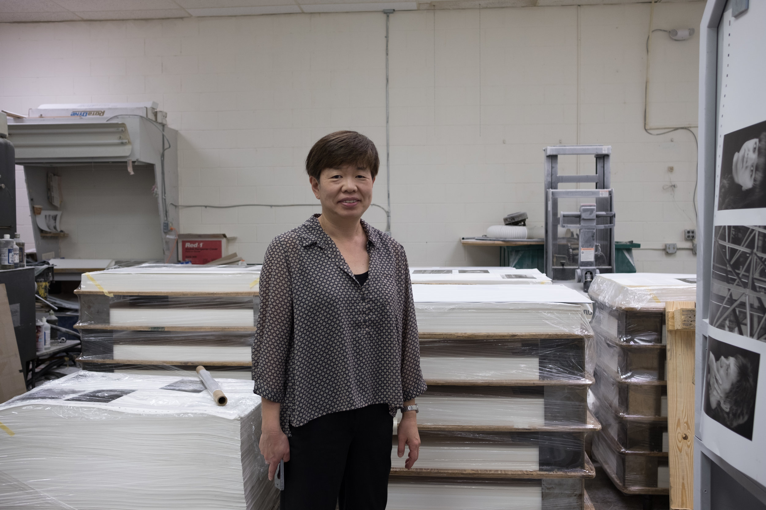 Yasuyo in front of palette with completed printed sheets