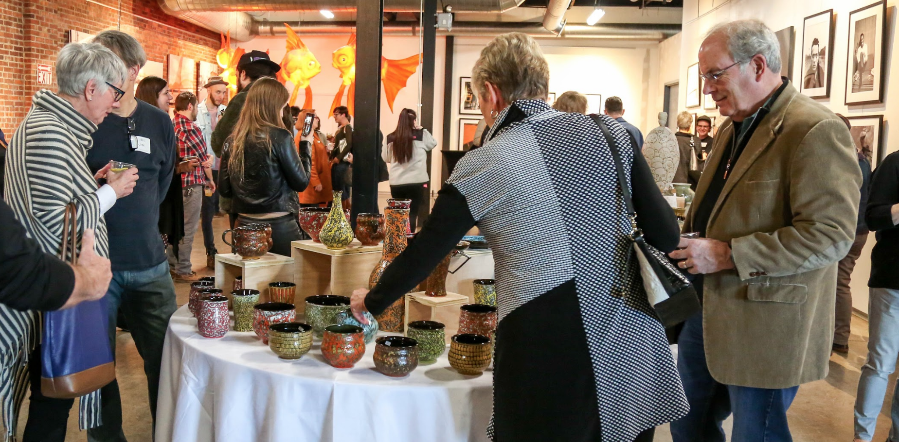 Guests of our Potters Market VIP Sneak Peek and First Pick event admiring Jim Gottuso 's pottery. March 2nd, 2018 | Copper and Kings  Photo: Erika Doll