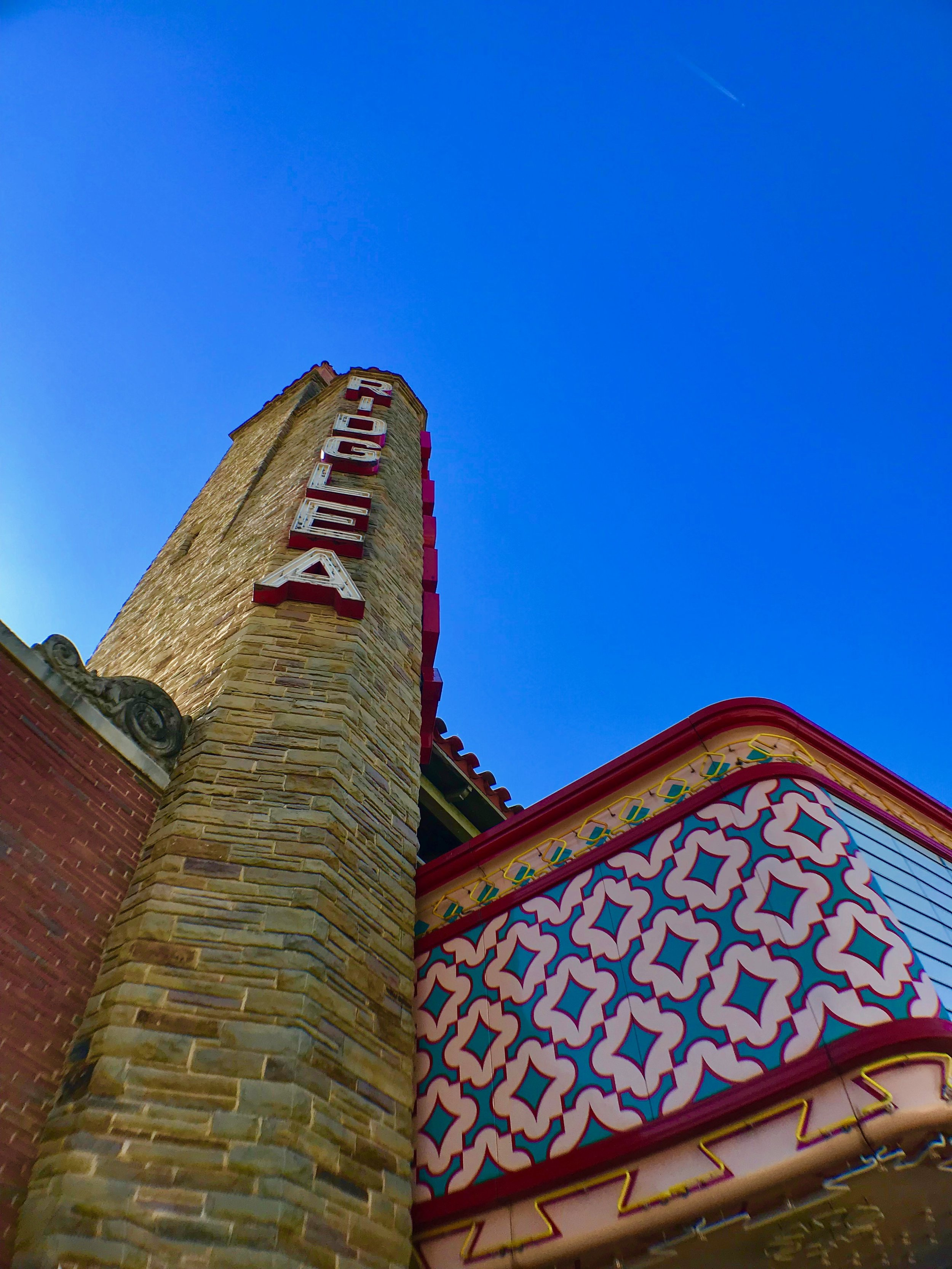 - Built in 1947 by Architect A.C. Luther, the beloved Ridglea Theater is now restored and re-living its former glory. The original 70-foot stone tower still stands as the iconic landmark of the west side, beckoning to all the DFW Metroplex. The Ridglea is located in the heart of the Camp Bowie District in Fort Worth. This charming neighborhood boasts fine dining, boutique shopping as well as the world-renowned Kimball Art Museum and The Modern.Since its beginning, a long list of nationally-acclaimed bands have made their mark in this legendary 20,000 square-foot historic venue. The Ridglea was once a premiere movie house featuring classic films of decades past. Now, thanks to the tireless efforts of new owner Jerry Shults, his daughter, Amy Herring and their associates, The Ridglea has been saved from demolition and listed on the National Registry of Historic Places, ensuring its legacy long into the future.In charge of restorations, Architect Sam Austin, of CMA Architecture, held The Ridglea restoration project close to his heart. Austin's father was the Chief Projectionist for the original Ridglea Theater build. Much of Sam's childhood was spent watching movies, cartoons, and newsreels at the Ridglea Theater.Today, The Ridglea is revived to its authentic allure, recovering the unique Spanish-Mediterranean elements. Details like the original terrazzo tile floor featuring the intricate compass rose. The panoramic mural, by famed artist Eugene Gilboe, captures your eyes the moment you step inside. Restored to its historical beauty, the main theater and grande balcony are reminiscent of old movie houses. Although The Ridglea Theater has the area's largest traditional movie screen, it also houses a state-of-the-art sound system and many modern amenities.Magnificently restored and newly renovated, The Ridglea now offers three options for events: The Ridglea Theater, The Ridglea Room & The Ridglea Lounge. The Ridglea is an ideal venue for film festivals, symphony orchest