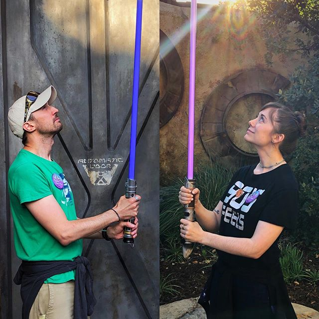 """Now that the """"secret"""" is out, we can share our favorite part of Galaxy's Edge: Getting our custom-built ENGAGEMENT LIGHTSABERS at Savi's Workshop!!! . Michael's is Peace and Justice themed with a blue kyber crystal. Mine is Elemental Nature themed with a purple kyber crystal. . Yes, they will make some form of an appearance at the wedding. You are welcome, and may the force be with you."""