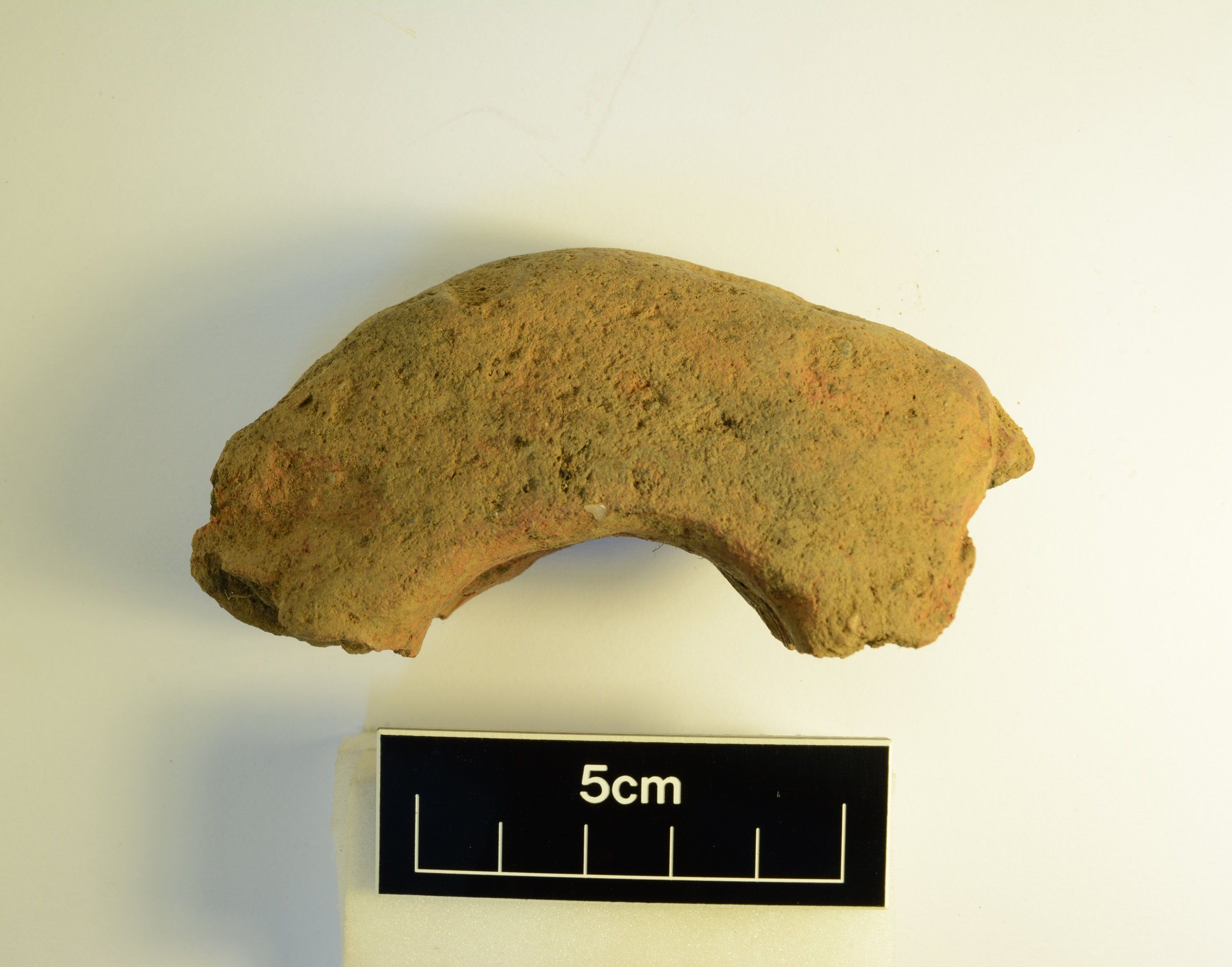 "Fragment of loom weight from SFB. Originally ""doughnut"" shaped, these fired-clay weights hold the warp threads on a loom taut while the weft is woven in."