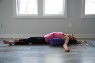 Supported Fish Pose (5 minutes)   Place a bolster or block shortways behind you to lower down where the bolster is resting at the mid-back. You may use your elbows to lower down. Hips are heavy, shoulders wrap around the prop to rest at the sides. Shoulders broaden. Allow head to rest on either a block or crown of the head rests on the floor, opening up through the throat and neck more. Knees can stay bent, extend, or find a butterfly shape.