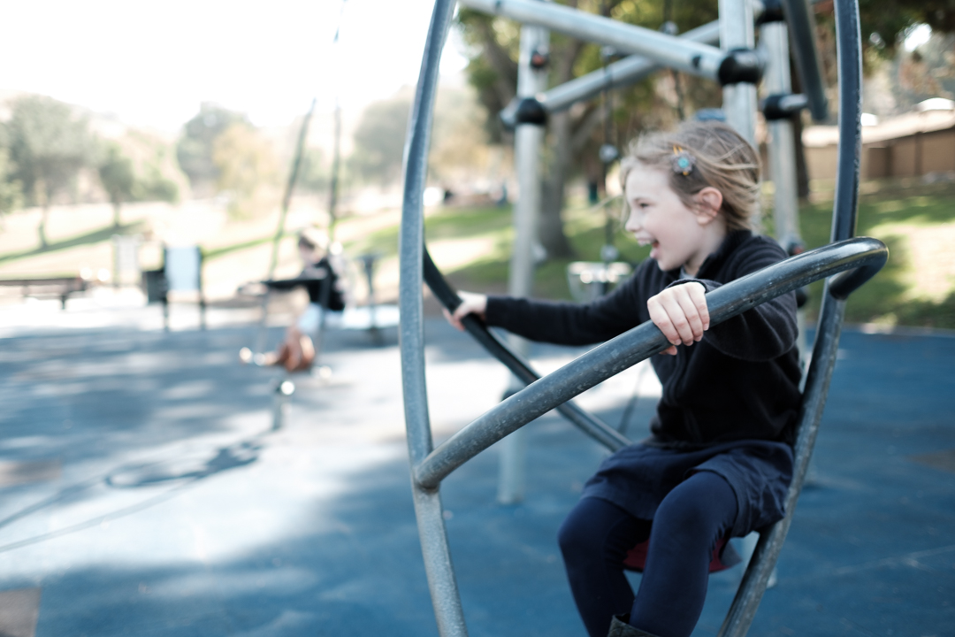 A sweet photo of a girl on playground equipment in San Dimas, CA by documentary photographer Erica Faith Walker.