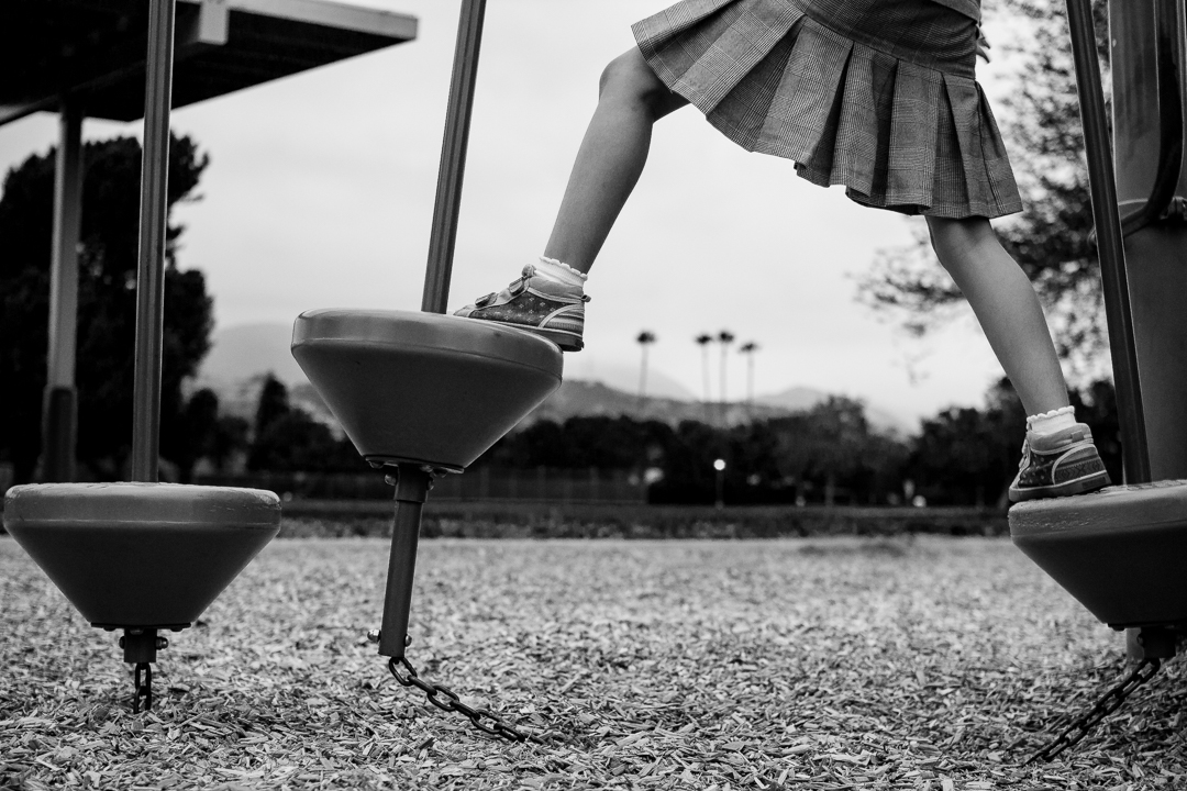Black and white photo of girl climbing on the playground equipment in Claremont, CA by Erica Faith Walker