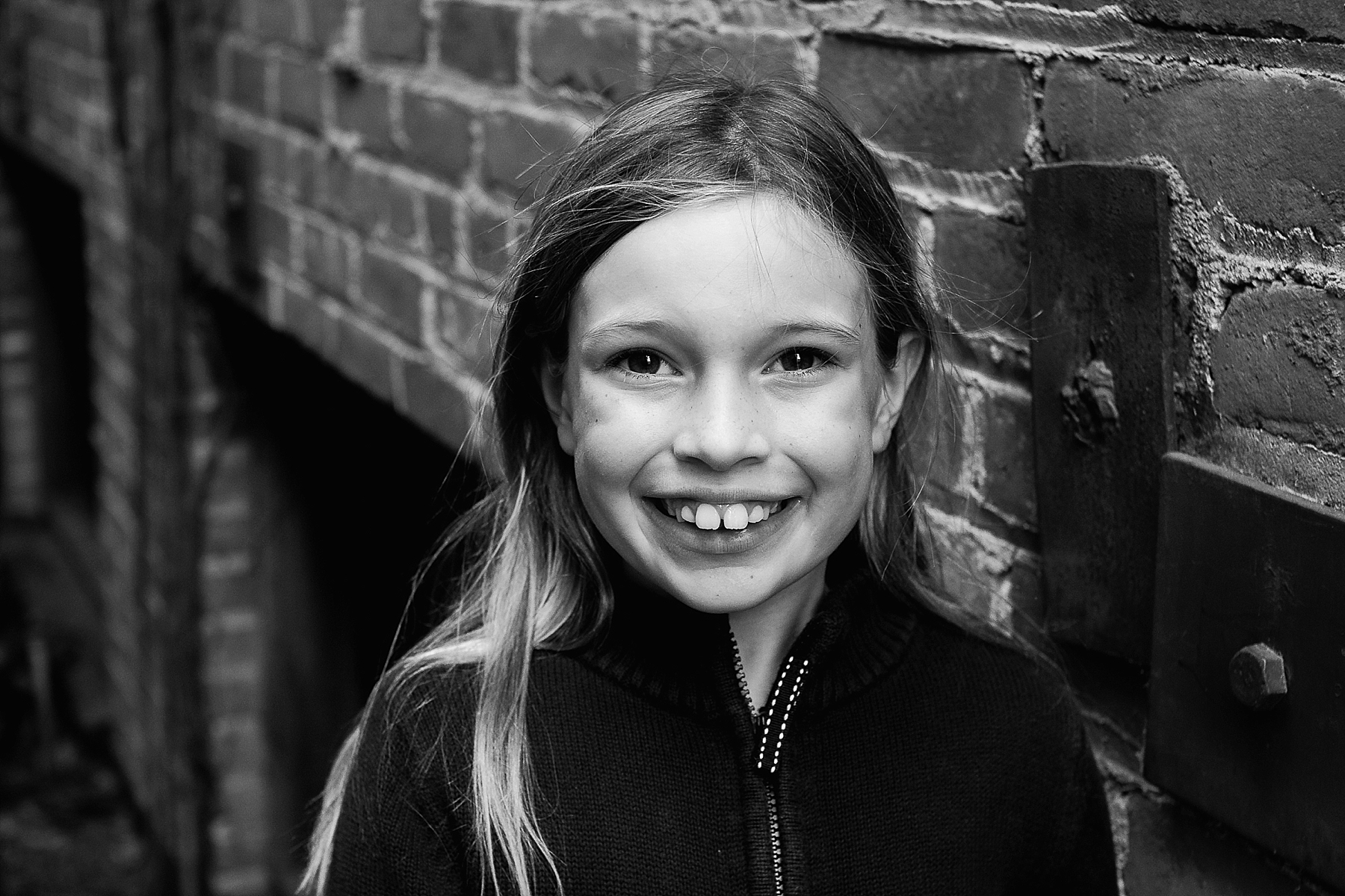 An urban black and white portrait of a girl next to a brick wall by Erica Faith Photography.