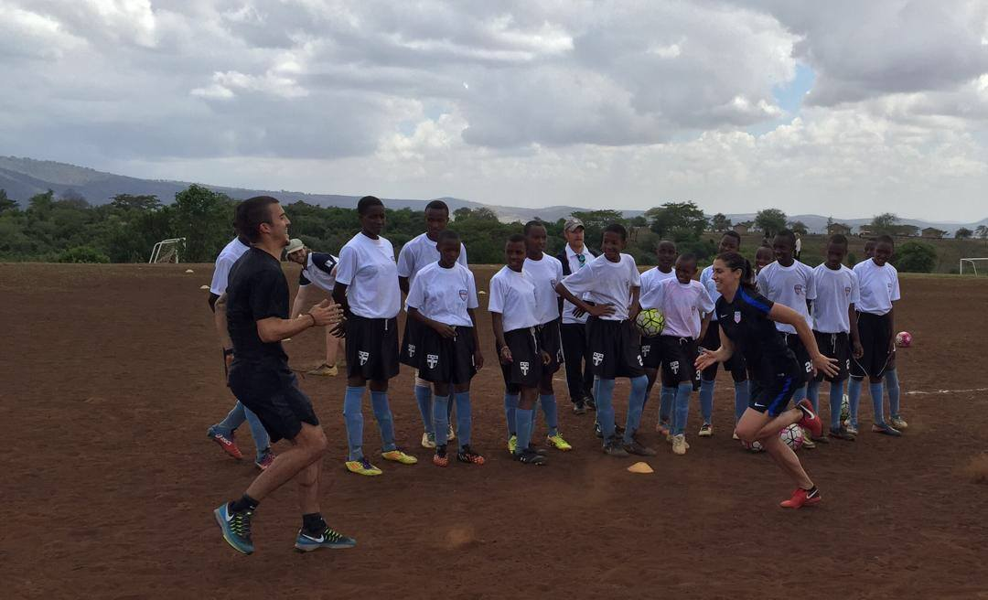 Sports Envoys and U.S. Women's National Team member, Alex Morgan, and Orlando City player Servando Carrasco demonstrate footwork in Tanzania.  2017.