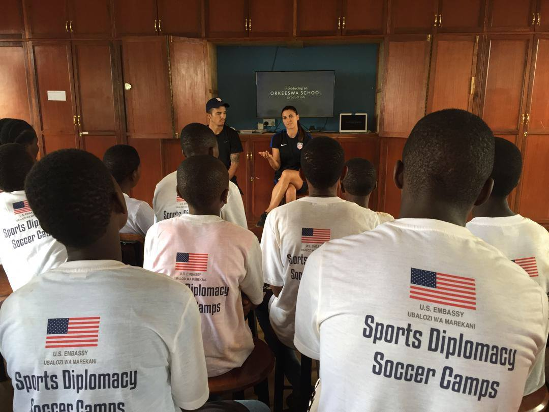 Sports Envoys and U.S. Women's National Team member, Alex Morgan, and Orlando City player Servando Carrasco demonstrate speak with youth in Tanzania. 2017.