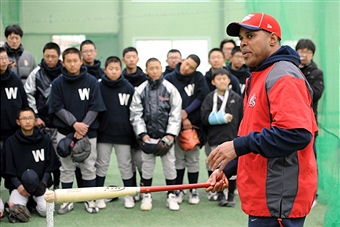 Sports Envoy Barry Larkin demonstrates batting technique with youth in Korea. 2011.