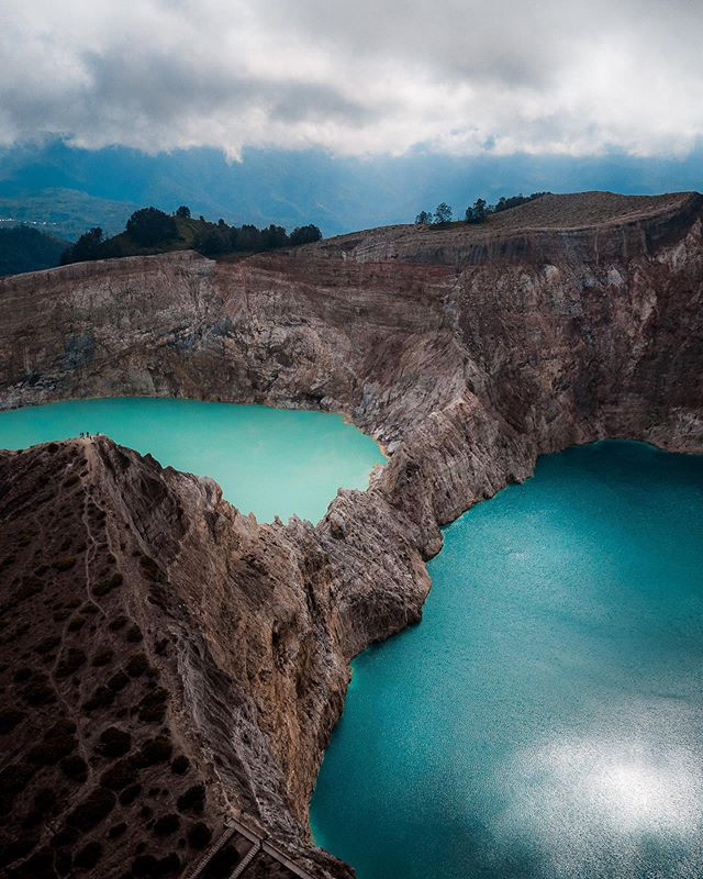 """Kelimutu is our final destination in the island of Flores. Inside this volcano are three crater lakes that differ in color. Locals believe these lakes are the final resting place for all souls, good and evil. The colors of the lake change depending on the amount of the volcanic gas and rainfall. When the conditions are right, the lake on the right of this image can turn blood red, giving it the name """"Villain's Lake."""" 💀🔥 #wonderfulindonesia #dji"""