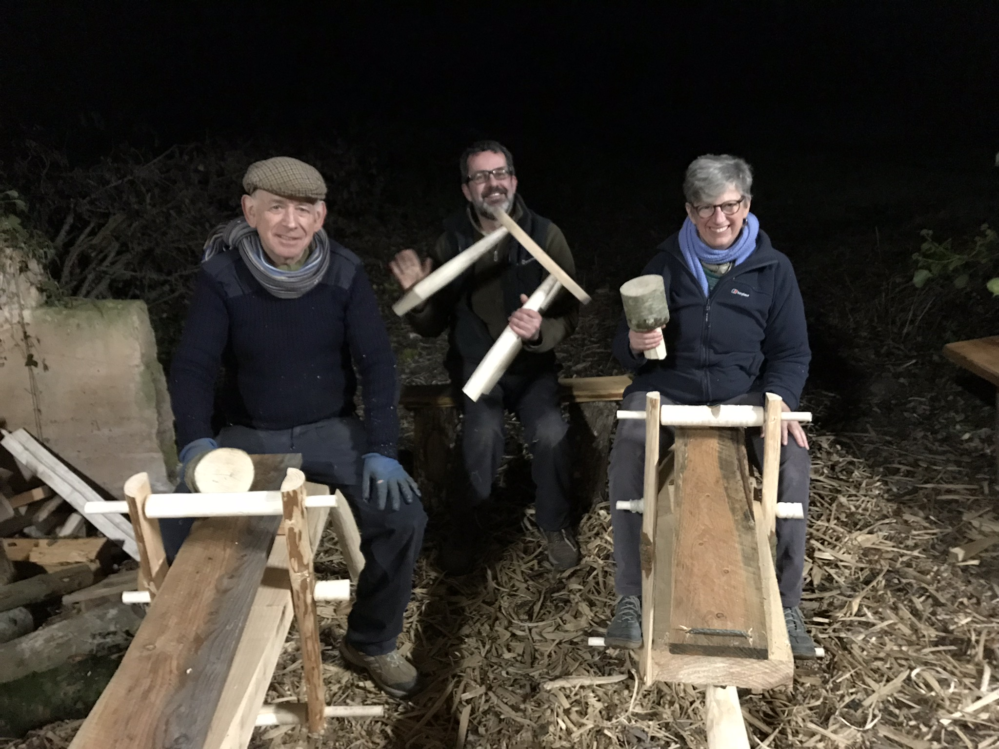Ian, and Jane sitting on their finished shave horses , and Jon in the background with his beech and ash stool/table.