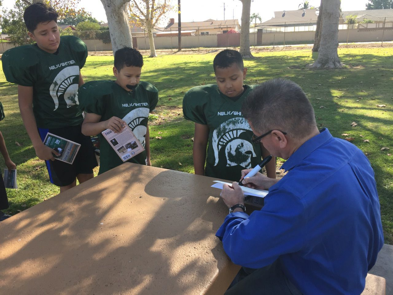 Barrio autographing books for kids in California Coach-Victor H Valdez Sr.jpg