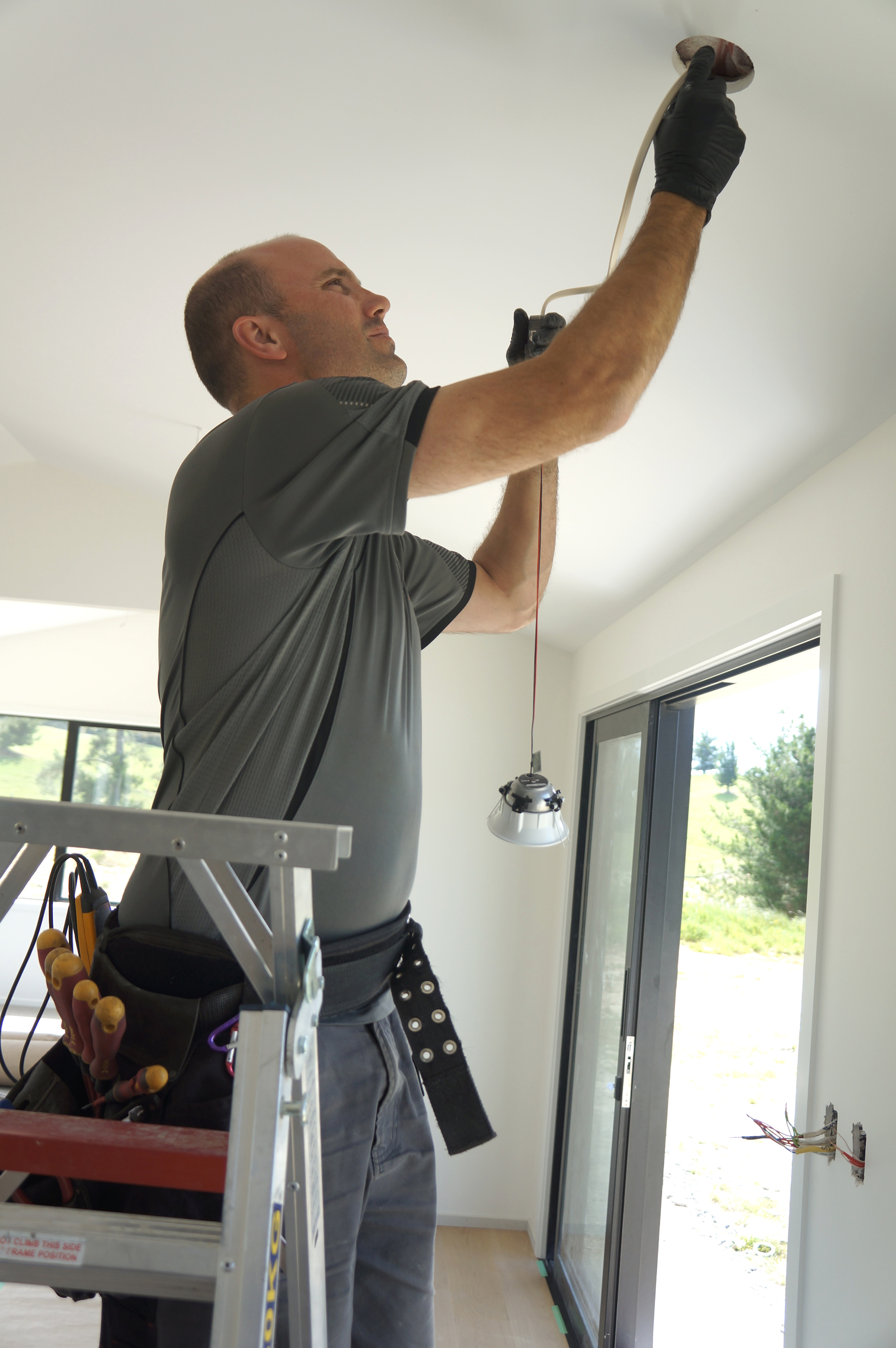 Josh Eves Registered Electrician installing a downlight