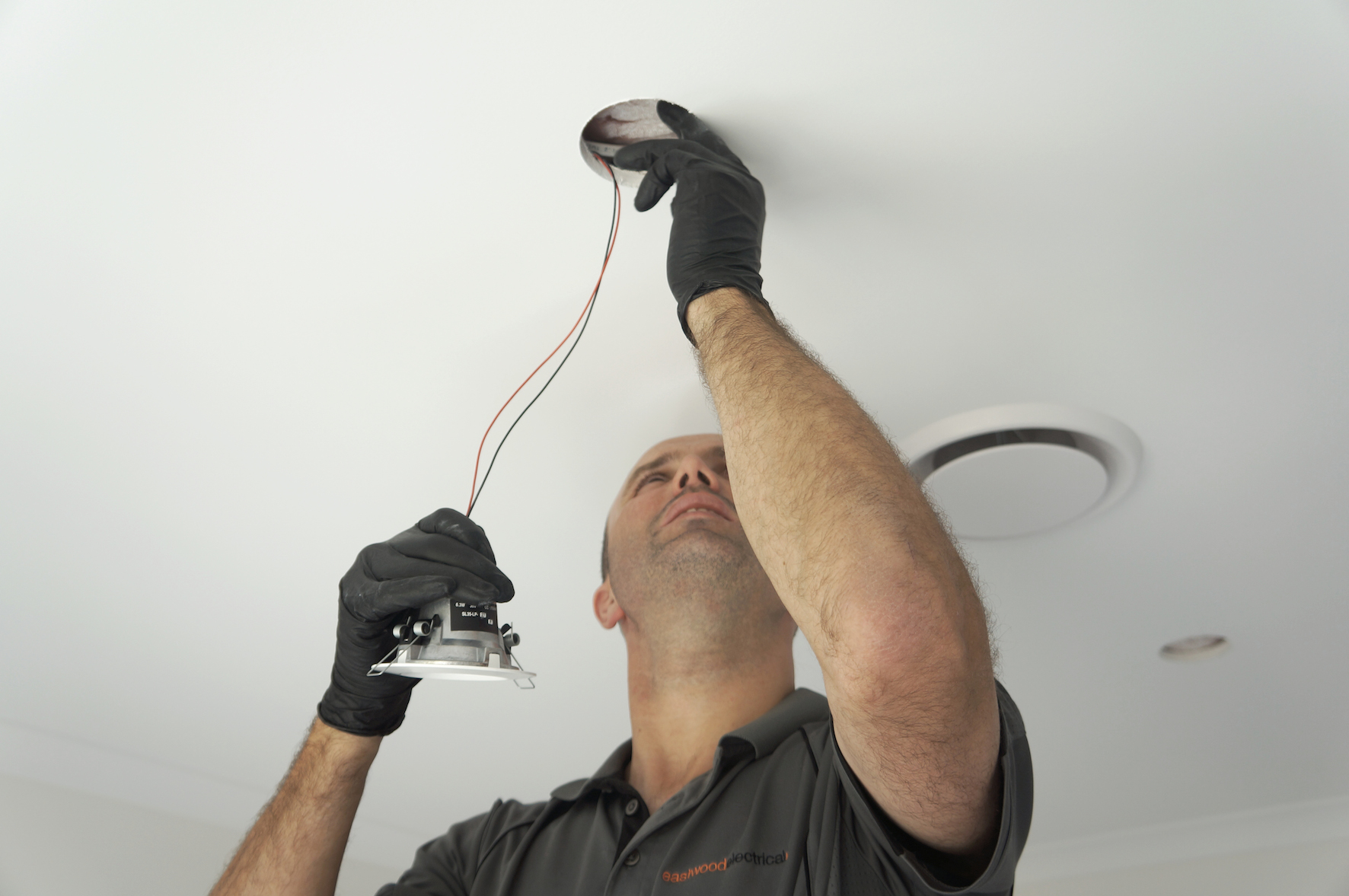 Josh Eves, Registered Electrician, installing a downlight