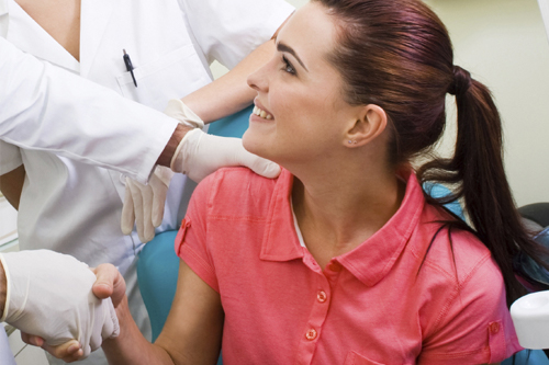 Doctor shaking female patients hand while she smiles