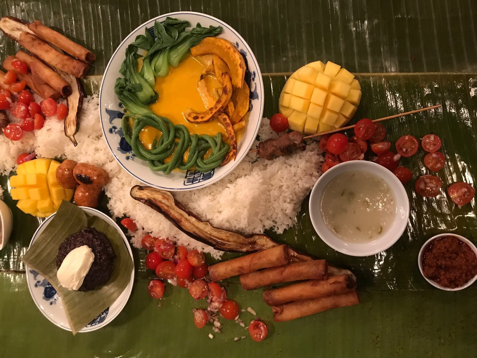 A kamayan is a communal-style Filipino feast, composed of colorful arrays of food that are usually served on banana leaves and eaten without utensils. / Bettina Makalintal for NPR