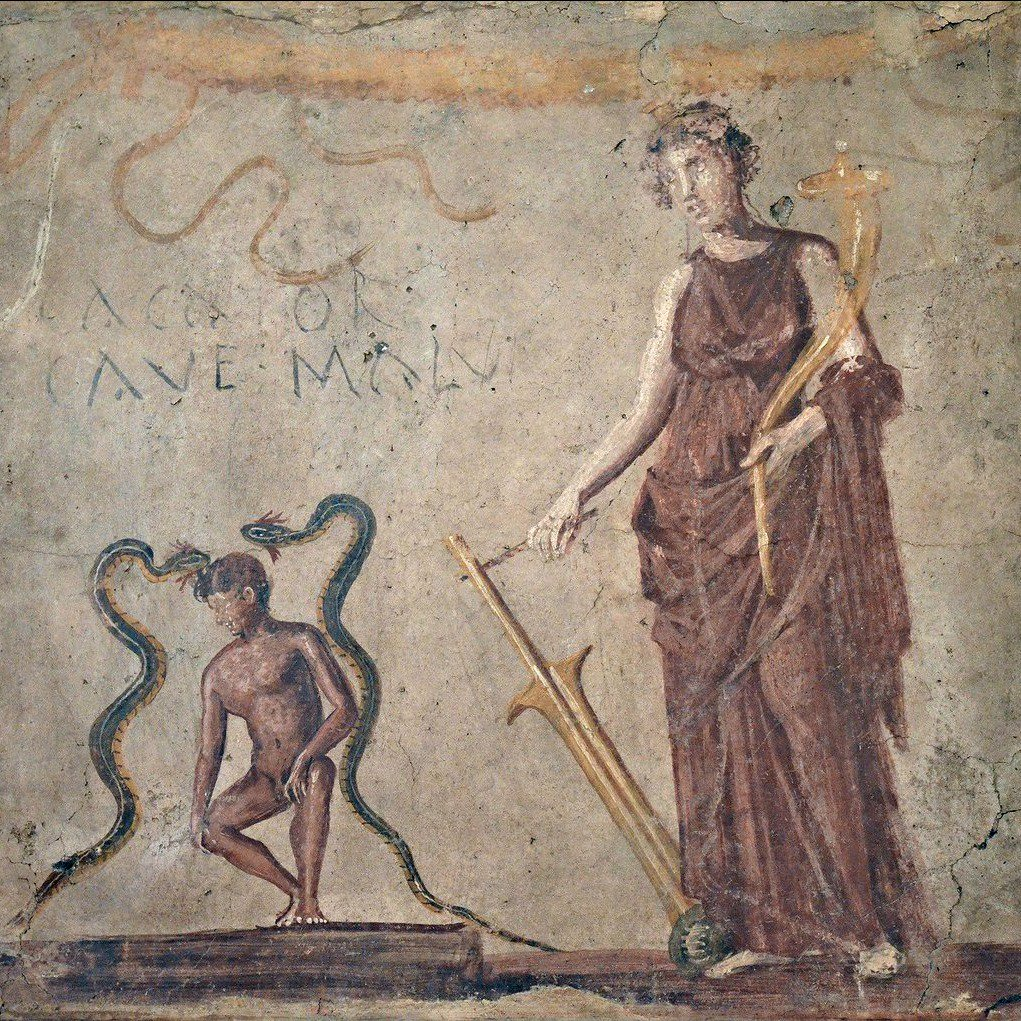 """The goddess Fortuna (or perhaps Venus of Pompeii) and two lucky snakes protect a naked youth squatting to poo. CACATOR CAVE MALUM means """"man doing a poo, beware evil!"""" From the National Archaeological Museum in Naples."""