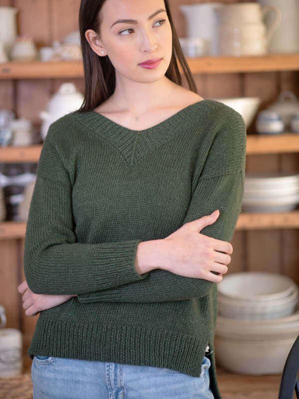 Model wearing a classic v-neck sweater in green