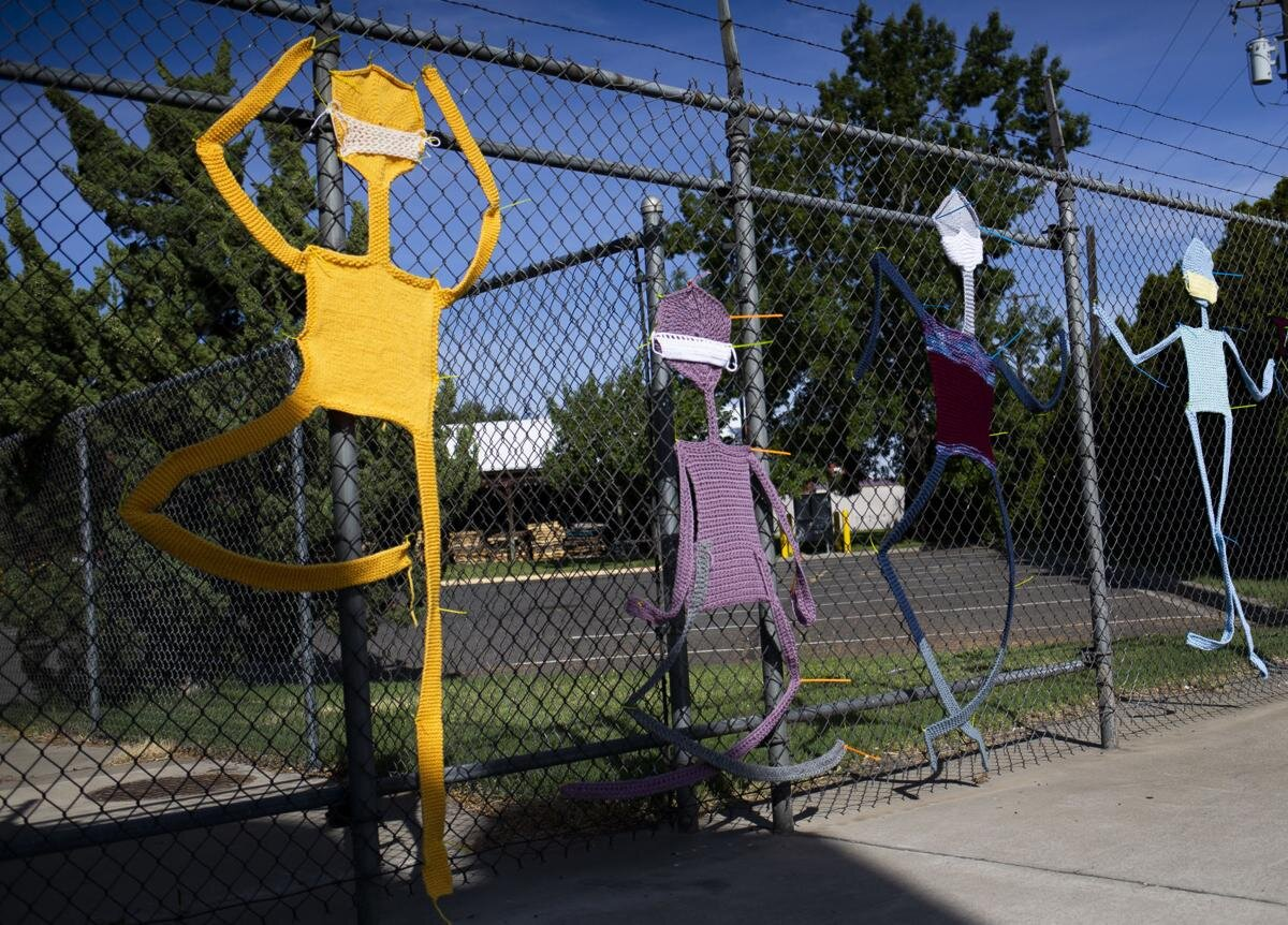 Knit and crocheted stick figures wearing masks, affixed to a fence