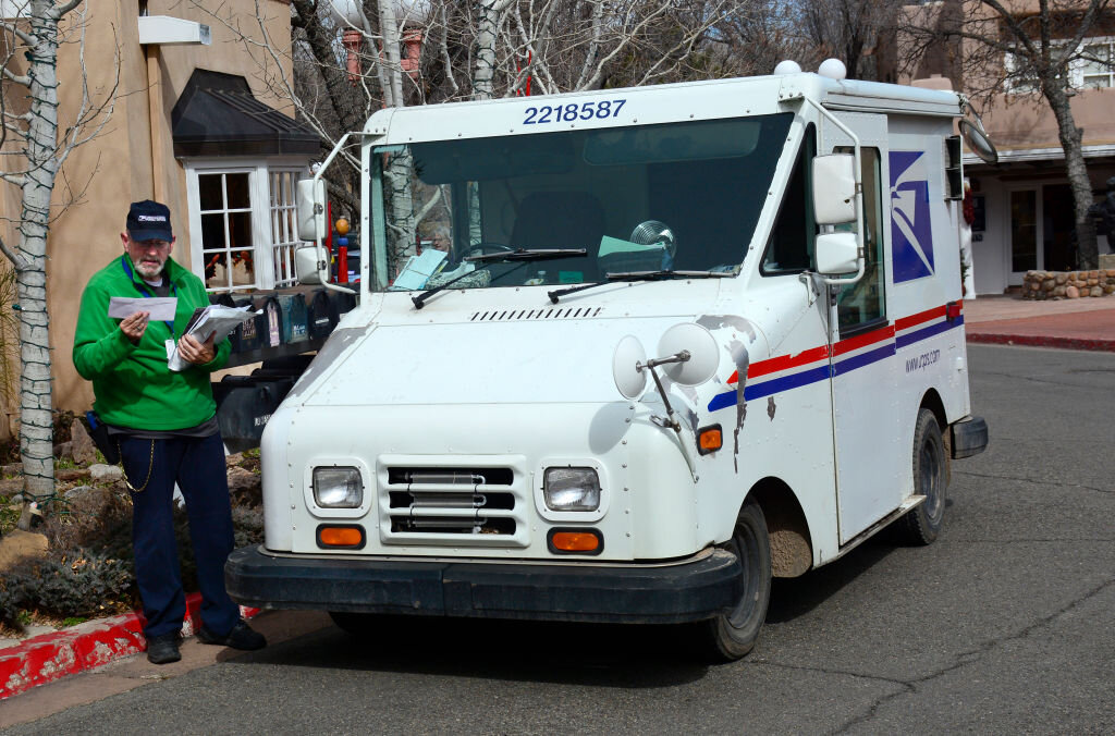 Letter carrier delivering mail while standing next to a postal truck