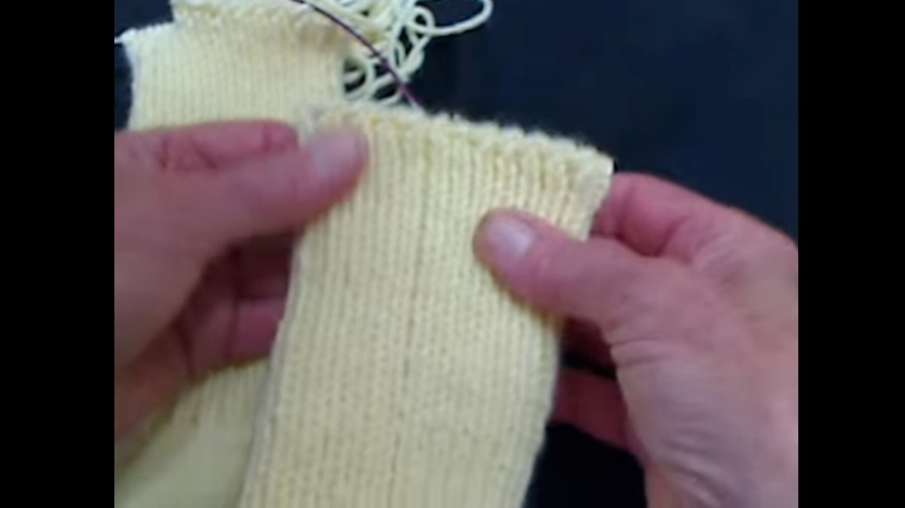 Screenshot from video of knitter showing the bound off top edge of a knitted yellow sock