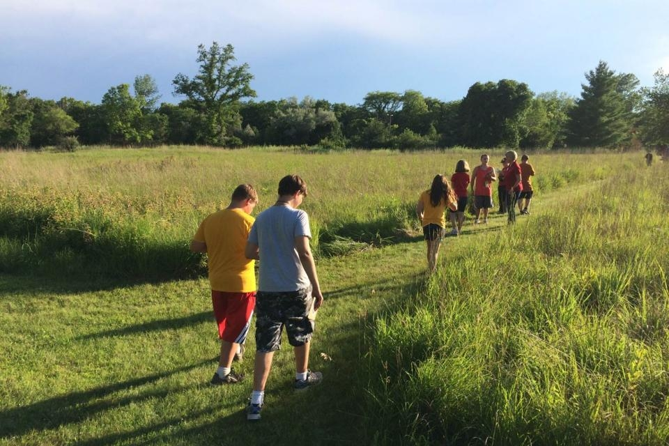 Walking through field at Clover Woods Camp & Retreat Center in Iowa.jpg