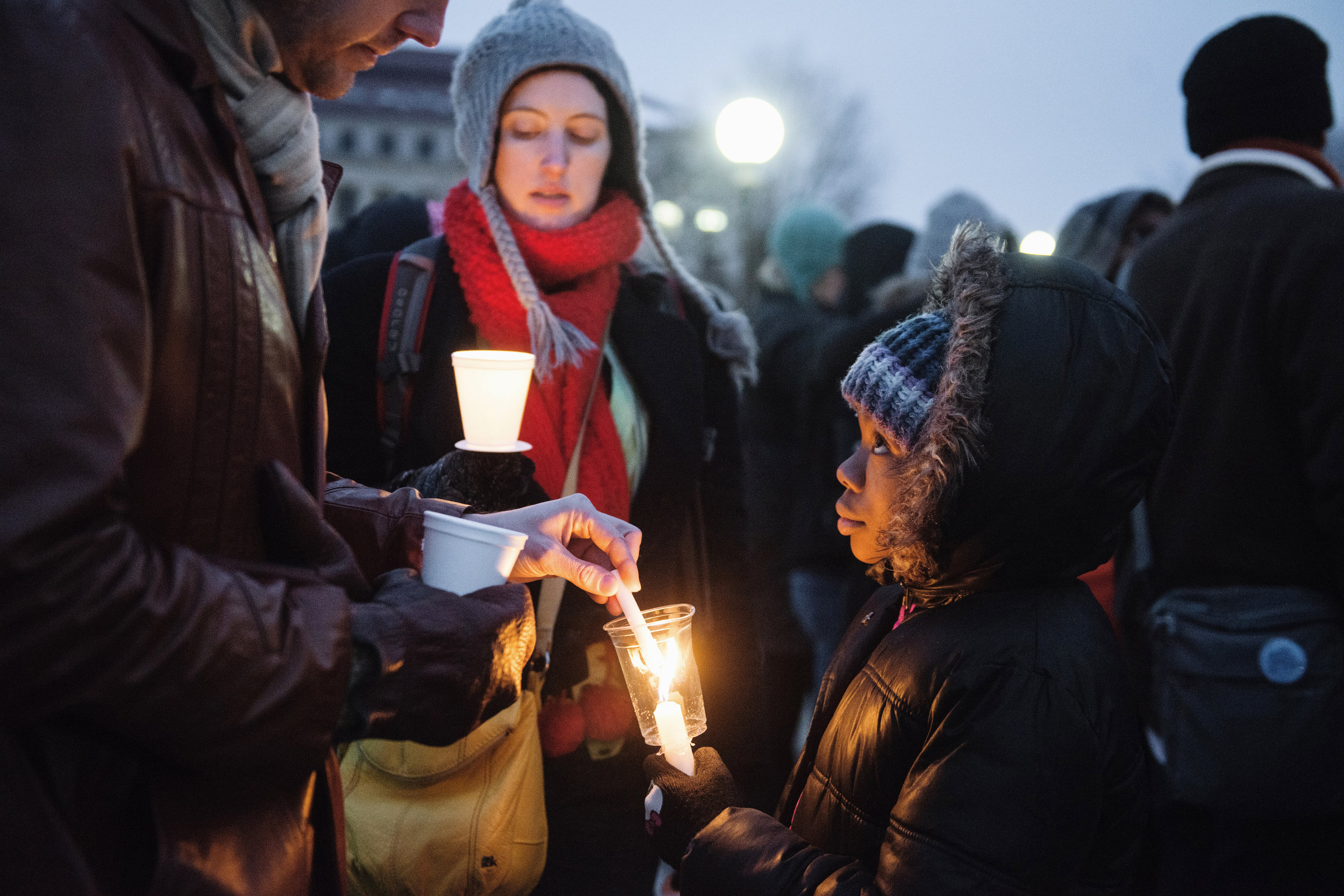 Khilanni Easterling helps ignite the candles of demonstrators in front of the Minnesota State Capitol on Martin Luther King Jr. Day, Jan. 19, 2015.