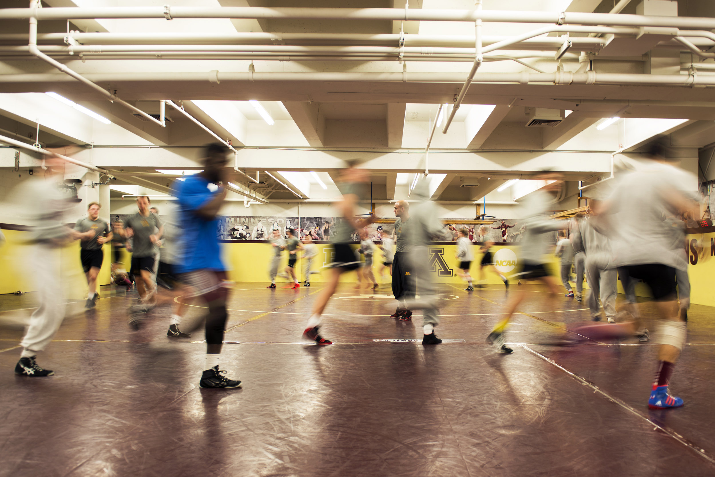 The wrestling team runs laps for a cardio warmup at the start of practice.