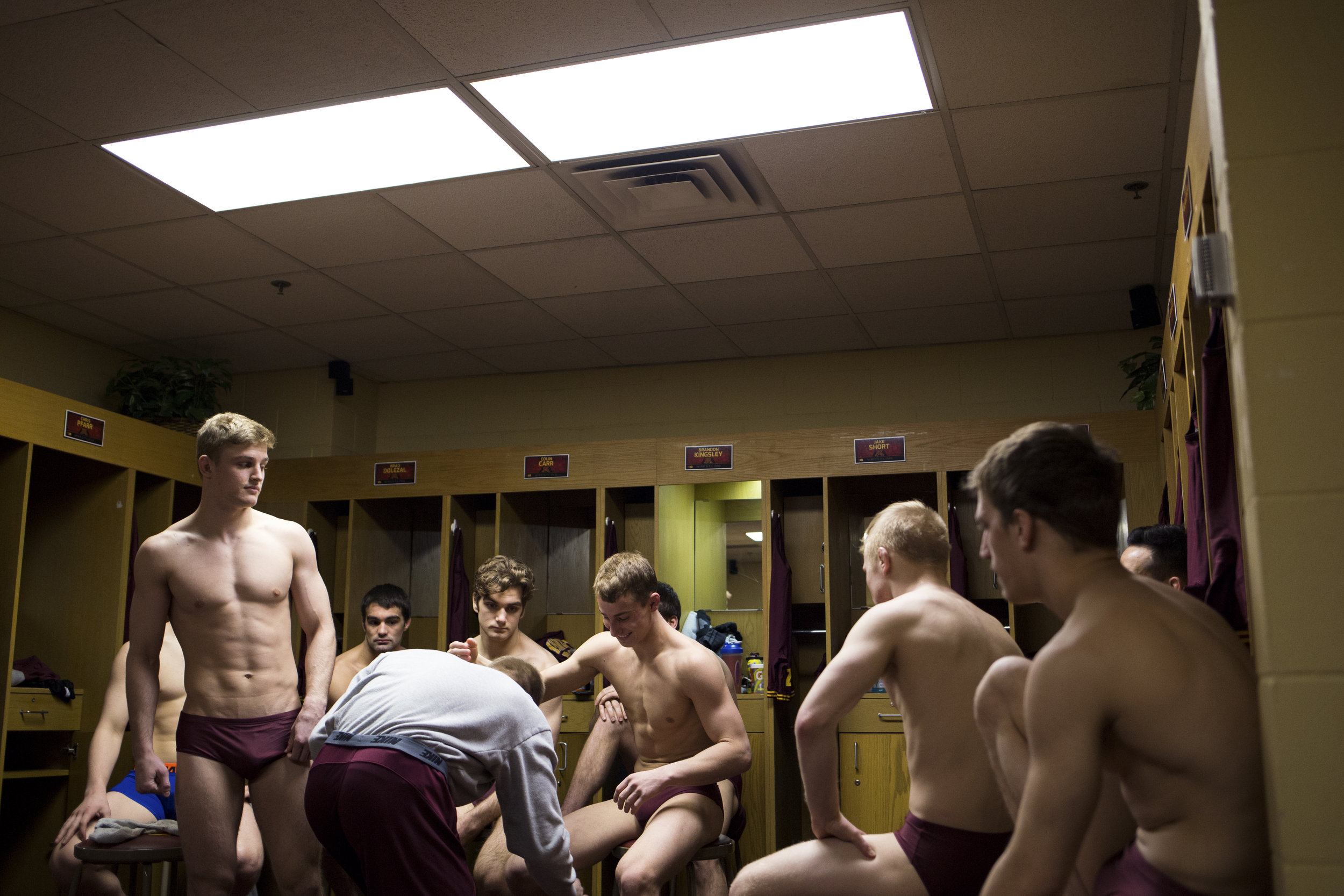 Stripped down to briefs, wrestlers await inspections and weigh-ins by a match official inside their locker room in the Sports Pavilion.