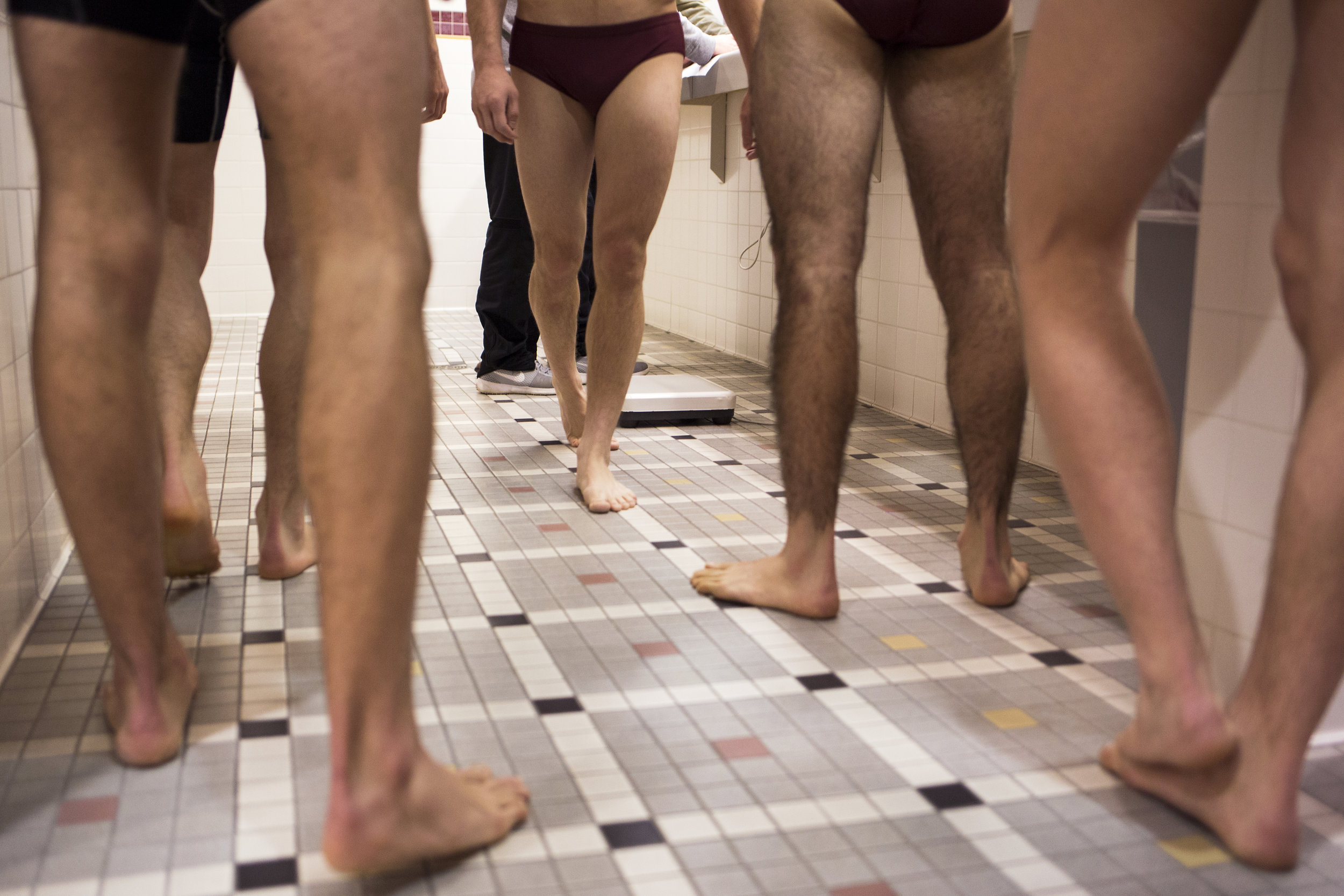 The wrestling team prepares to step onto the scale to be weighed by an official. Within the hour before each competition, officials make sure that each athlete's weight does not exceed the limit for his competitive class.