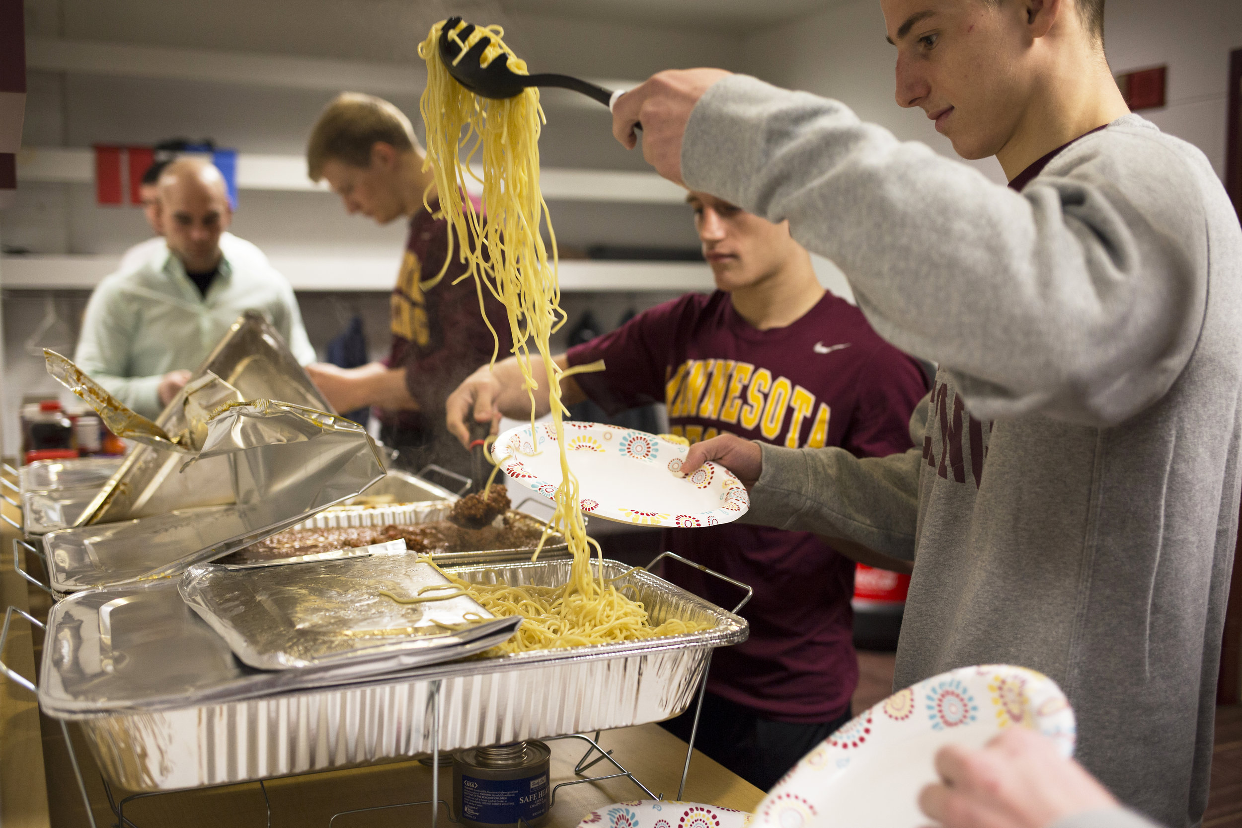 After their weigh-in, wrestlers fuel themselves with a hot meal for their dual meet, less than an hour away.