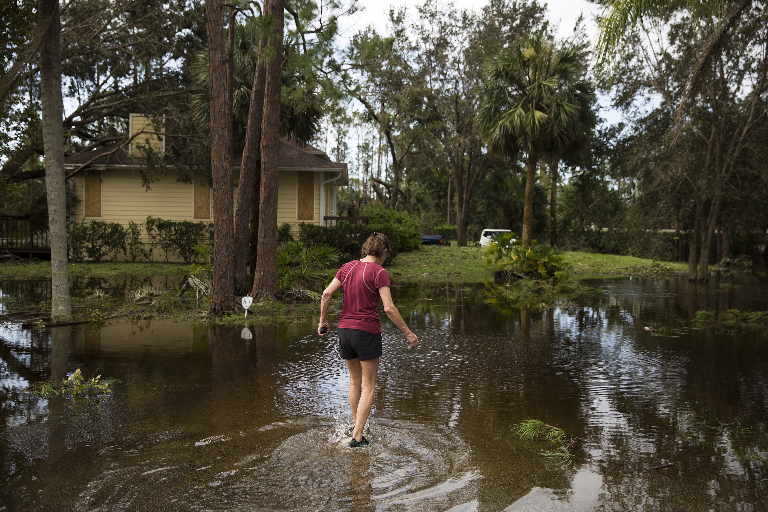 Barbara Rice steps through her flooded yard after assessing damage on her property caused by Hurricane Irma in North Naples on Monday, September 11, 2017.