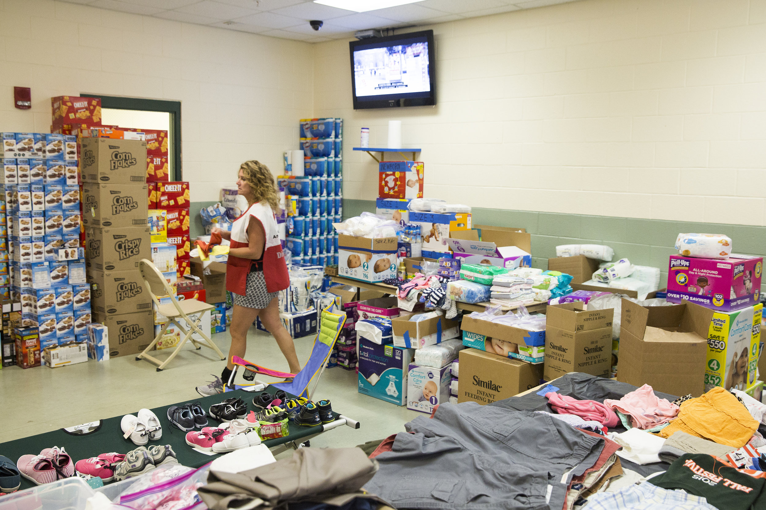 Volunteer Nicci Garcia works to manage a room of food, clothing and hygiene supplies at the American Red Cross' shelter in the Estero Recreational Center on Wednesday, September 20, 2017.