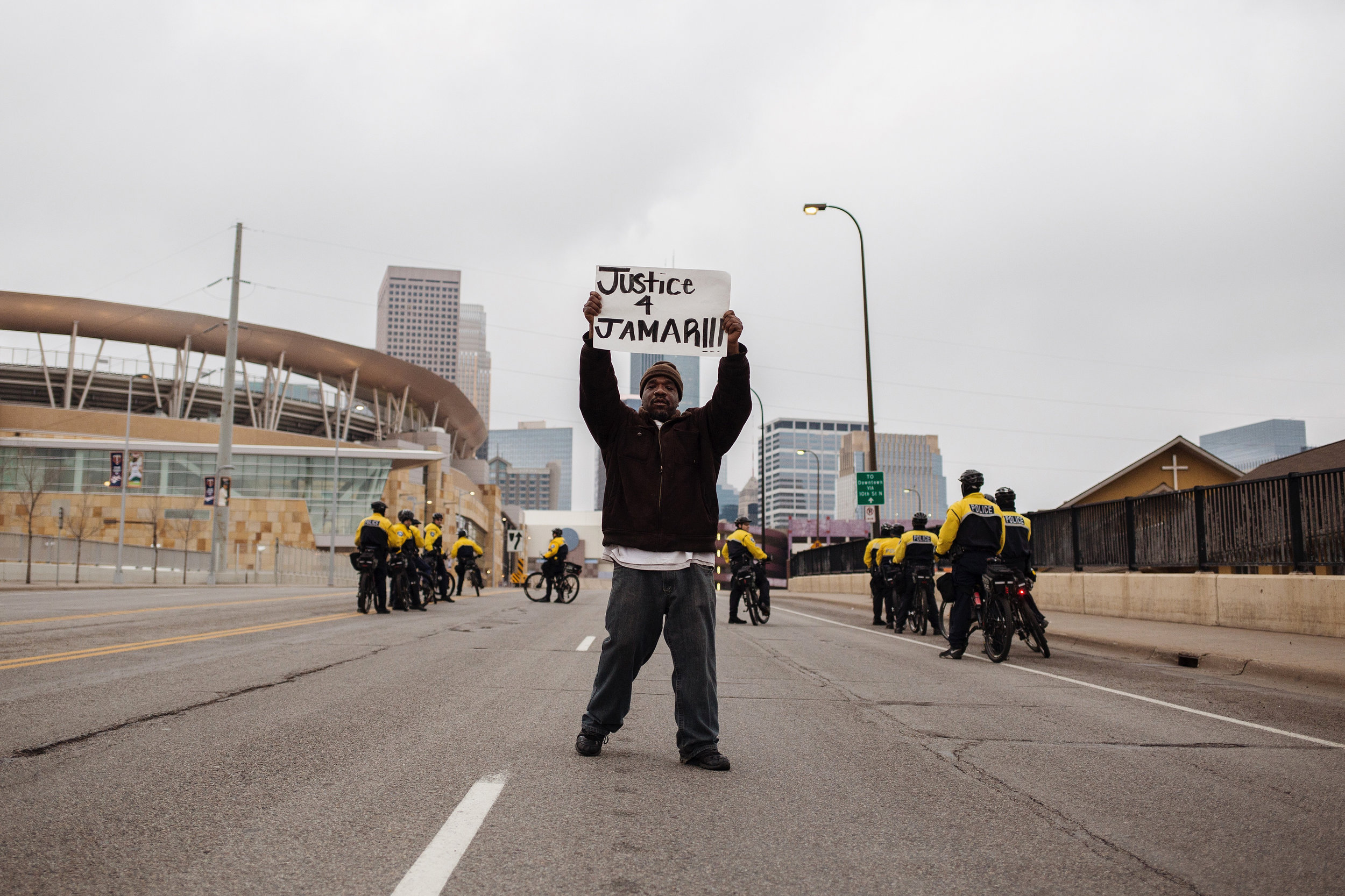 Donnie Straub, 42, of north Minneapolis holds up a sign at the front of the demonstrators as they marched towards the Hennepin County Government Center on Wednesday, March 30, 2016.